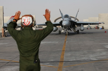 U.S. Marine plane captain with Marine Fighter Attack Squadron 232, Special Purpose Marine Air-Ground Task Force—Crisis Response—Central Command, directs an F/A-18 Hornet preparing for a strike mission in Southwest Asia, June 9, 2015. Pilots of VMFA-232 support Combined Joint Task Force—Operation Inherent Resolve with a combination of surveillance flights and kinetic strike missions, enabling Iraqi Security Forces in their fight against the Islamic State of Iraq and the Levant. (U.S. Marine Corps Photo by Cpl. Leah Agler/Released)