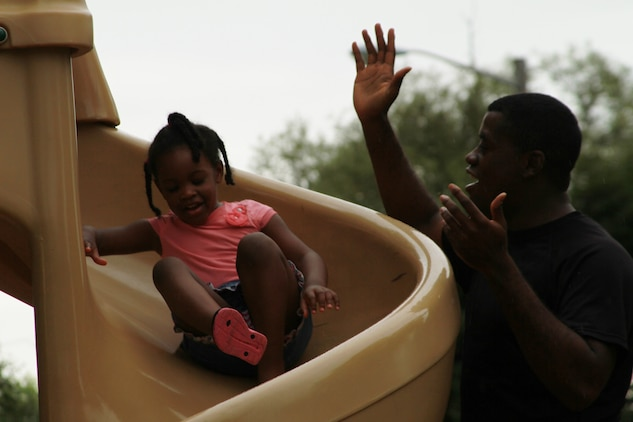U.S. Marine Corps Sgt. Kevin C. Bland, a native of Joiner, Arkansas and canvasing recruiter for Recruiting Sub-Station Madison Heights, encourages his daughter Karmen, as she slips down a slide during Recruiting Station Detroit's annual family day at Memorial Park in Royal Oak, Michigan, Aug. 8, 2015. Each one of RS Detroit's 11 RSSs attended the event with their families. (U.S. Marine Corps photo by Sgt. Joshua Heins/Released)