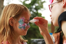 Amelia Franklin closes her eyes while getting her face painted during Marine Corps Recruiting Detroit's annual family day at Memorial Park in Royal Oak, Michigan, Aug. 8, 2015. The family day consisted of multiple activities for the Marines and their families to include a bounce house, face painting, arts and crafts, sports, an outdoor playground and the recognition of jobs well done in the months of June and July. (U.S. Marine Corps photo by Sgt. Joshua Heins/Released)