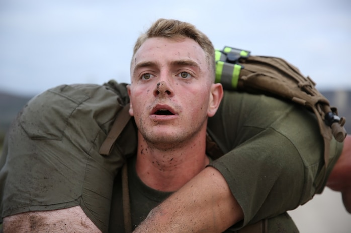 A Marine assigned to Company K, 3rd Battalion, 5th Marine Regiment, 1st Marine Division, conducts buddy squats as part of the Dark Horse Ajax Challenge aboard Marine Corps Base Camp Pendleton, Calif., Aug. 20, 2015. The eight-mile course tested the Marines' and Sailors' endurance and leadership skills with trials spread across the San Mateo area. (U.S. Marine Corps photo by Cpl. Will Perkins)