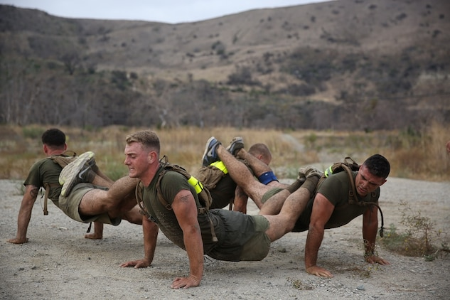 Marines assigned to Company K, 3rd Battalion, 5th Marine Regiment, 1st Marine Division, work together to complete fire team pushups as part of the Dark Horse Ajax Challenge aboard Marine Corps Base Camp Pendleton, Aug. 20, 2015. The eight-mile course tested the Marines' and Sailors' endurance and leadership skills with trials spread across the San Mateo area. (U.S. Marine Corps photo by Cpl. Will Perkins)