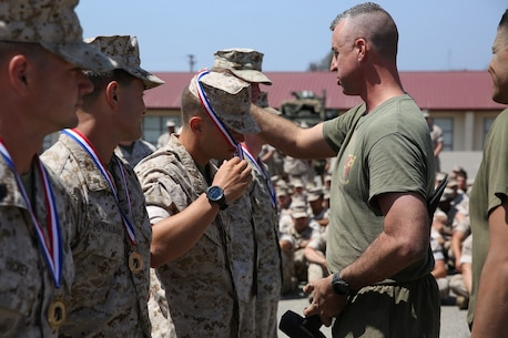 Lieutenant Colonel Hunter Rawlings, battalion commander, 3rd Battalion, 5th Marine Regiment, 1st Marine Division, presents the first place medals to the Marines with Company L, 3/5, 1st Mar. Div., after completing the Dark Horse Ajax Challenge aboard Marine Corps Base Camp Pendleton, Calif., Aug. 20, 2015. The eight-mile course tested the Marines' and Sailors' endurance and leadership skills with trials spread across the San Mateo area. (U.S. Marine Corps photo by Cpl. Will Perkins)