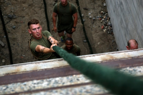 A Marine assigned to Company K, 3rd Battalion, 5th Marine Regiment, 1st Marine Division, climbs a rope as part of the Dark Horse Ajax Challenge aboard Marine Corps Base Camp Pendleton, Calif., Aug. 20, 2015. The eight-mile course tested the Marines' and Sailors' endurance and leadership skills with trials spread across the San Mateo area. (U.S. Marine Corps photo by Cpl. Will Perkins)