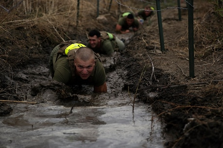 Marines assigned to Company K, 3rd Battalion, 5th Marine Regiment, 1st Marine Division, low-crawl through a trench during the Dark Horse Ajax Challenge aboard Marine Corps Base Camp Pendleton, Calif., Aug. 20, 2015. The eight-mile course tested the Marines' and Sailors' endurance and leadership skills with trials spread across the San Mateo area. (U.S. Marine Corps photo by Cpl. Will Perkins)