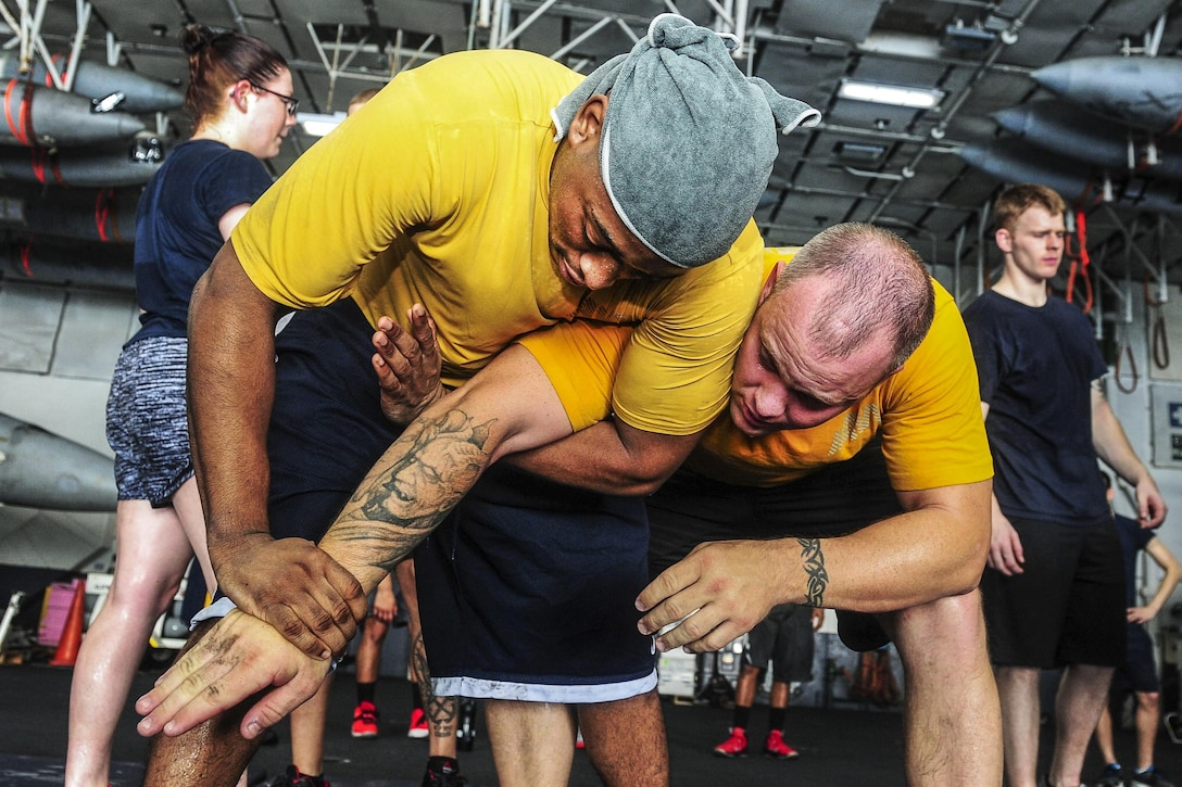 U.S. Navy Petty Officer 2nd Class Jamall Shuford performs a mechanical advantage control hold on Master-at-Arms 1st Class Joey Lawrence during a security forces training class in the hangar bay aboard the aircraft carrier USS Theodore Roosevelt in the Arabian Gulf, Aug. 20, 2015. The carrier is in the U.S. 5th Fleet area of operations supporting Operation Inherent Resolve, which include strike operations in Iraq and Syria as directed. U.S. Navy photo by Petty Officer 3rd Class Taylor L. Jackson