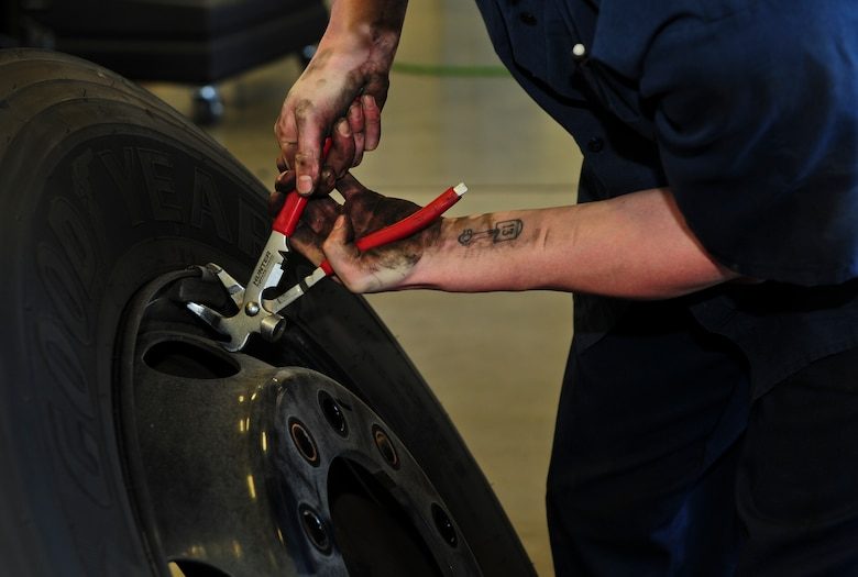 U.S. Air Force Senior Airman Kenneth Stanley, 355th Logistics Readiness Squadron Vehicle Management Flight customer service center vehicle maintenance journeyman, removes a wheel weight at Davis-Monthan Air Force Base Ariz., Aug. 19, 2015. Wheel weights are used to properly balance wheels and tires after they've been mounted together. (U.S. Air Force photo by Airman 1st Class Chris Drzazgowski/Released)