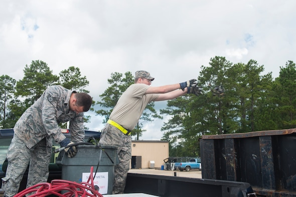 U.S. Air Force Staff Sgt. Albert Lucas (left) and Senior Airman Justin Pennuell, 23d Equipment Maintenance Squadron armament technicians, dispose of scrap metal at the recycling center Aug. 20, 2015, at Moody Air Force Base, Ga. Moody's recycling program contributes to minimizing negative impacts on the environment and earns the base approximately $20,000 annually. (U.S. Air Force photo by Airman 1st Class Ceaira Tinsley/Released)