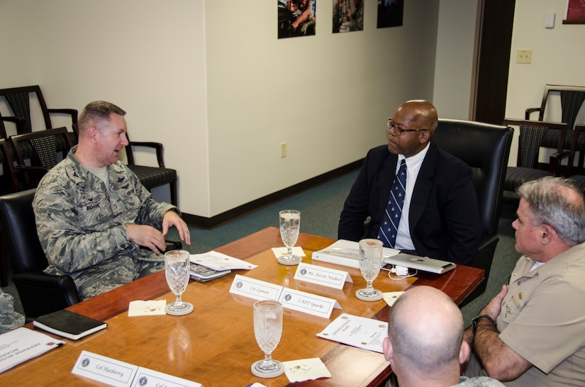 (Middle) Kevin Walker, Defense Business Board member, receives a brief from Joint Base Charleston leadership, August 20, 2015 at JB Charleston – Air Base, S.C. The Defense Business Board provides the Secretary and Deputy Secretary of Defense, as well as other senior leaders, trusted independent and objective advice reflecting a private sector perspective on proven and effective best business practices for potential application to the Department. (U.S. Air Force photo/Staff Sgt. AJ Hyatt)