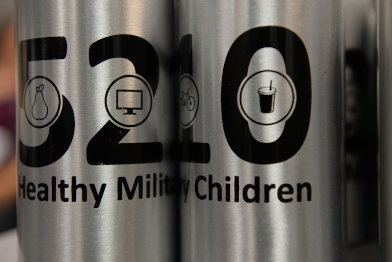 Water bottles with the 5210 Healthy Military Children program logo sit during a cooking class called 'EMFP Garden to Table Cooking Class', August 6, 2015 at Scott Air Force Base, Illinois. The HMC program's goal is to reduce screen time, add one hour of activity, and eat five servings of fruits and vegetables each day. (U.S. Air Force photo by Airman 1st Class Erica Holbert-Siebert)