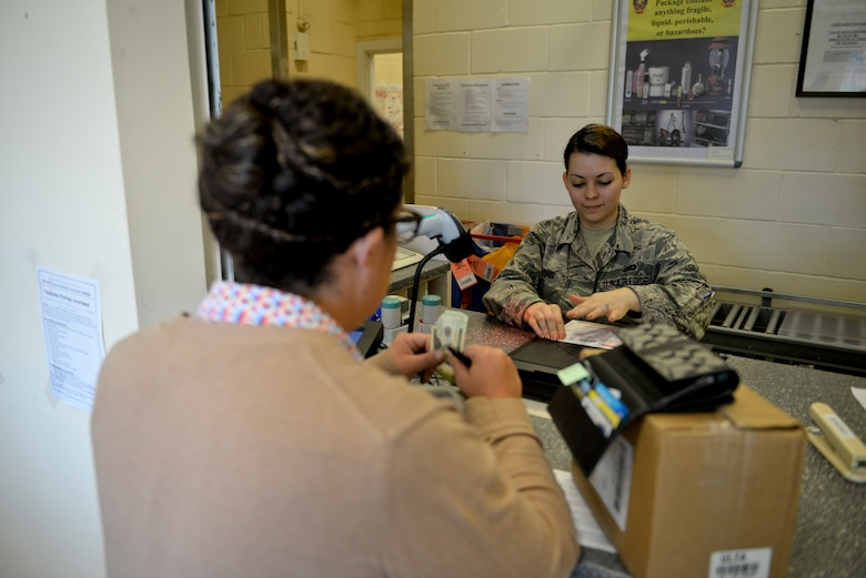 U.S. Air Force Airman Payton Blevins, 100th Communication Squadron finance clerk from Holbrook, Ariz., processes a parcel for Kristin Fagot, 488th Intelligence Squadron training manager from Laguna Niguel, Calif., Aug. 19, 2015, at the base post office on RAF Mildenhall, England. On Sept. 1, 2015, the base post office will implement a new process to only accept printed customs forms. A computer station will be added to the lobby for customers to use. (U.S. Air Force photo by Staff Sgt. Micaiah Anthony/Released)