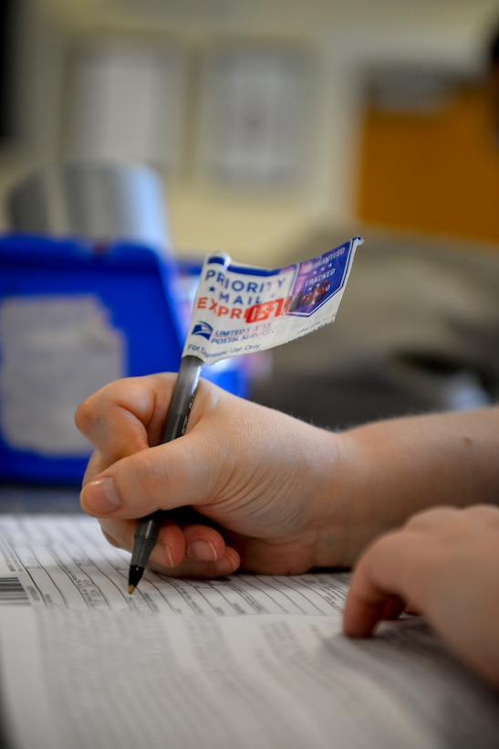 Aimee Evans, 488th Intelligence Squadron language analyst from Cleveland, fills out a customs form Aug. 19, 2015, at the base post office on RAF Mildenhall, England. On Oct. 1, 2015, the United States Postal Service will only accept customs forms that have been printed out. To help ease the transition the base post office will start implementing the process on Sept. 1, 2015. (U.S. Air Force photo by Staff Sgt. Micaiah Anthony/Released)