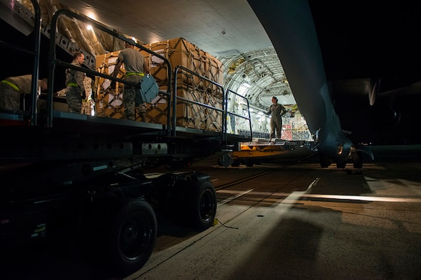 Airmen from the 305th Ariel Port Squadron load a C-17 Globemaster III with rations for Thule Air Base, Greenland on the flight line of Joint Base McGuire-Dix-Lakehurst, N.J. August 18, 2015. The joint base is the closest and only base that's sends rations to Thule. (U.S. Air Force photo by Airman 1st Class Joshua King)