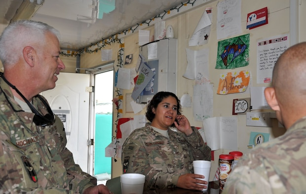 """Chaplain (Lt. Col.) Bryan Hochhalter and Tech. Sgt. Sandra Alvor-Thrash, talk to Train, Advise, Assist Command-Air (TAAC-Air) personnel in the """"Gratitude Café"""" during their weekly rounds to work centers at Forward Operating Base Oqab Aug. 16, 2015. Hochhalter is deployed to Kabul, Afghanistan, from the U.S. Air Force Academy in Colorado Springs, Colorado. Alvor-Thrash is deployed from Eglin Air Force Base, Florida. (U.S. Air Force photo/Master Sgt. Barbara Fuller)"""