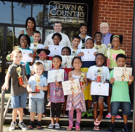 Officials pose with children who showcase their trophies and certificates following Marine Corps Logistics Base Albany's 2015 Summer Reading Program awards ceremony, Aug. 22. Held at the installation's Town and Country Restaurant Grand Ballroom, top readers in four different age groups received trophies and all of the participants received certificates as their parents watched or photographed them.