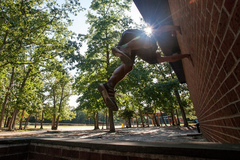 """Tech. Sgt. Justin B. Gielski performs a flip on a wall while training to compete on the TV show """"American Ninja Warrior"""" at a playground near his home in Medford, N.J., Aug. 21, 2015. Gielski placed fifth in the all-military city final on the TV show and advanced to the finals in Las Vegas. Gielski is a loadmaster with the 150th Special Operations Squadron, 108th Wing, New Jersey Air National Guard, located at Joint Base McGuire-Dix-Lakehurst, N.J. (U.S. Air National Guard photo by Master Sgt. Mark C. Olsen/Released)"""