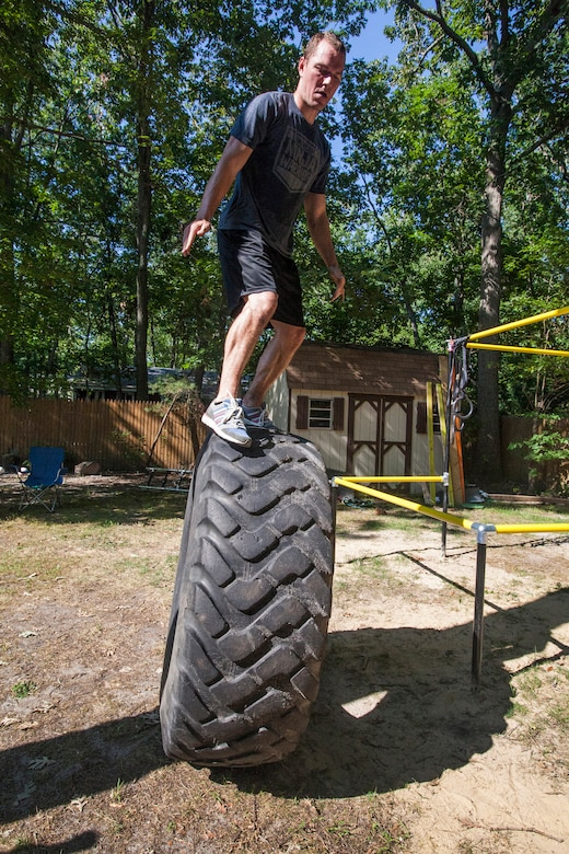 "Tech. Sgt. Justin B. Gielski balances on a tire while training to compete on the TV show ""American Ninja Warrior"" in the backyard of his home in Medford, N.J., Aug. 21, 2015. Gielski placed fifth in the all-military city final on the TV show and advanced to the finals in Las Vegas. Gielski is a loadmaster with the 150th Special Operations Squadron, 108th Wing, New Jersey Air National Guard, located at Joint Base McGuire-Dix-Lakehurst, N.J. (U.S. Air National Guard photo by Master Sgt. Mark C. Olsen/Released)"