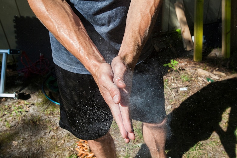 """Tech. Sgt. Justin B. Gielski rubs chalk dust on his hands while training to compete on the TV show """"American Ninja Warrior"""" in the backyard of his home in Medford, N.J. Aug. 21, 2015. Gielski placed fifth in the all-military city final on the TV show and advanced to the finals in Las Vegas. Gielski is a loadmaster with the 150th Special Operations Squadron, 108th Wing, New Jersey Air National Guard, located at Joint Base McGuire-Dix-Lakehurst, N.J. (U.S. Air National Guard photo by Master Sgt. Mark C. Olsen/Released)"""