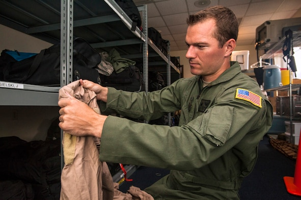 """Tech. Sgt. Justin B. Gielski, a loadmaster with the 150th Special Operations Squadron, 108th Wing, New Jersey Air National Guard, checks his deployment bag at Joint Base McGuire-Dix-Lakehurst, N.J., Aug. 19, 2015. Gielski placed fifth in the all-military city final on the TV show """"American Ninja Warrior"""" and advanced to the finals in Las Vegas. (U.S. Air National Guard photo by Master Sgt. Mark C. Olsen/Released)"""
