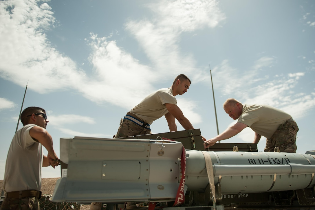 U.S. Air Force Airman 1st Class Matthew Lopez, center, 62nd Expeditionary Reconnaissance Squadron munitions systems technician, unpacks a GPS-guided GBU-49 weapon at Kandahar Airfield, Afghanistan, Aug. 15, 2015.  The 62nd ERS Munitions Flight ensures that every munition loaded onto an MQ-1 Predator and MQ-9 Reaper will perform as expected when used. (U.S. Air Force photo by Tech. Sgt. Joseph Swafford/Released)