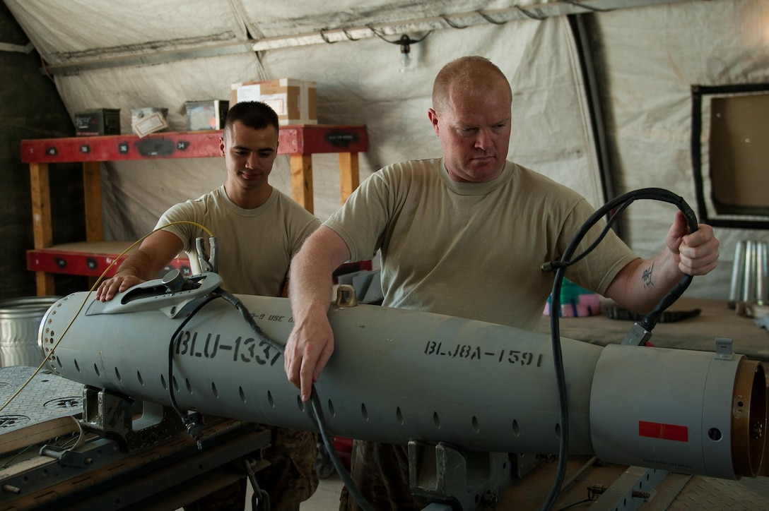 U.S. Air Force Airman 1st Class Matthew Lopez, left, 62nd Expeditionary Reconnaissance Squadron munitions systems technician, helps build a GPS-guided GBU-49 weapon at Kandahar Airfield, Afghanistan, Aug. 15, 2015.  The 62nd ERS Munitions Flight ensures that every munition loaded onto an MQ-1 Predator and MQ-9 Reaper will perform as expected when used. (U.S. Air Force photo by Tech. Sgt. Joseph Swafford/Released)