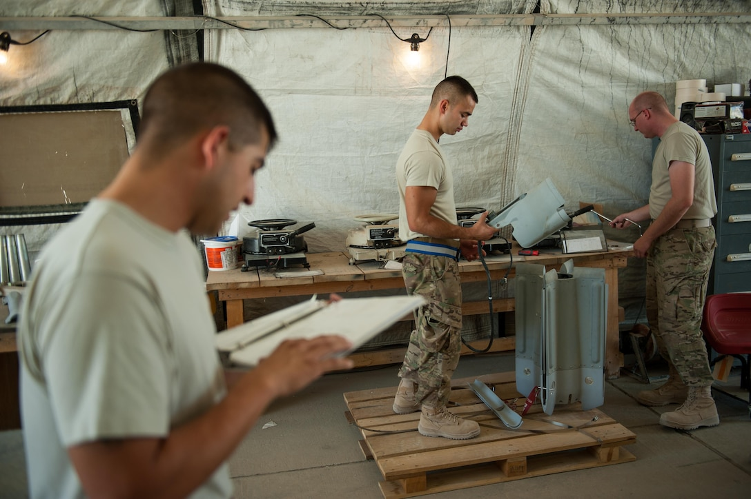 U.S. Air Force Airman 1st Class Matthew Lopez, center, 62nd Expeditionary Reconnaissance Squadron munitions systems technician, builds a GPS-guided GBU-49 weapon at Kandahar Airfield, Afghanistan, Aug. 15, 2015.  The 62nd ERS Munitions Flight ensures that every munition loaded onto an MQ-1 Predator and MQ-9 Reaper will perform as expected when used. (U.S. Air Force photo by Tech. Sgt. Joseph Swafford/Released)