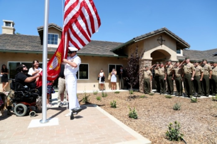 Marines from 1st Explosive Ordnance Disposal Company, 1st Marine Logistics Group look on as retired Staff Sgt. Jason Ross raises the national and Marine Corps colors in front of a new home dedicated to him and his family by The Gary Sinise Foundation. Ross was injured by an improvised explosive device in Afghanistan in 2011 while serving as an explosive ordnance disposal technician and lost both of his legs as a result. The new home has smart technology that will significantly reduce the difficulty of everyday tasks for Ross and allow him and his family to live more comfortably.