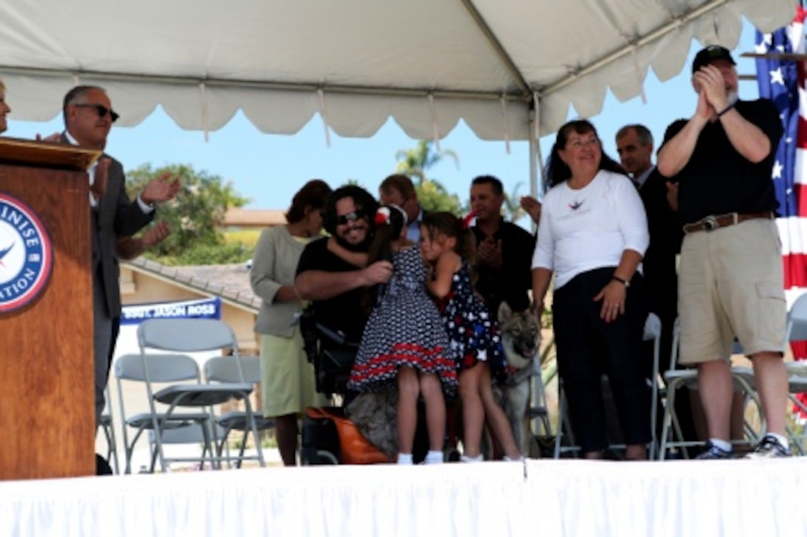 Retired Staff Sgt. Jason Ross hugs his two daughters, Jackie and Stacie, during a ceremony where a new home was presented to him and his family by The Gary Sinise Foundation and their Restoring Independence Supporting Empowerment program dedicated to helping wounded veterans. Ross was injured by an improvised explosive device in Afghanistan in 2011 while serving as an explosive ordnance disposal technician and lost both of his legs as a result. The new home has smart technology that will significantly reduce the difficulty of everyday tasks for Ross and allow him and his family to live more comfortably.