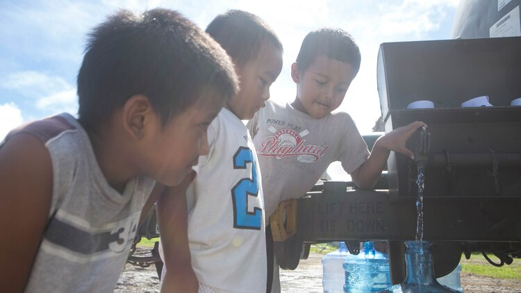 Young boys fill a water jug while U.S. Marines with Combat Logistics Battalion 31, 31st Marine Expeditionary Unit, distribute water to local civilians during typhoon relief efforts in Saipan, Aug. 19, 2015. The Marines with Echo Company, Battalion Landing Team 2nd Battalion, 5th Marines, 31st MEU and CLB 31, 31st MEU, assisted the locals of Saipan by producing and distributing potable water. The Marines and sailors of the 31st MEU were conducting training near the Mariana Islands when they were redirected to Saipan after the island was struck by Typhoon Soudelor Aug. 2-3.