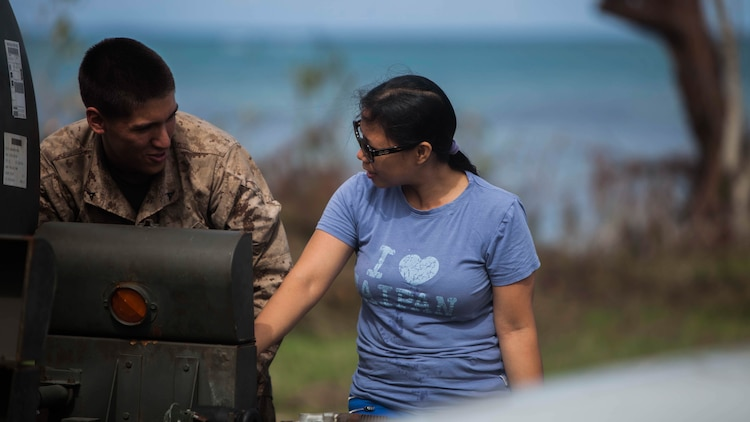 U.S. Marine Lance Cpl. Andy Larsen, with Combat Logistics Battalion 31, 31st Marine Expeditionary Unit, helps distribute water to local civilians during typhoon relief efforts in Saipan, Aug. 13, 2015. The Marines with Echo Company, Battalion Landing Team 2nd Battalion, 5th Marines, 31st MEU and CLB 31, 31st MEU, are aiding the locals of Saipan by producing and distributing potable water. The Marines and sailors of the 31st MEU were conducting training near the Mariana Islands when they were redirected to Saipan after the island was struck by Typhoon Soudelor Aug. 2-3.