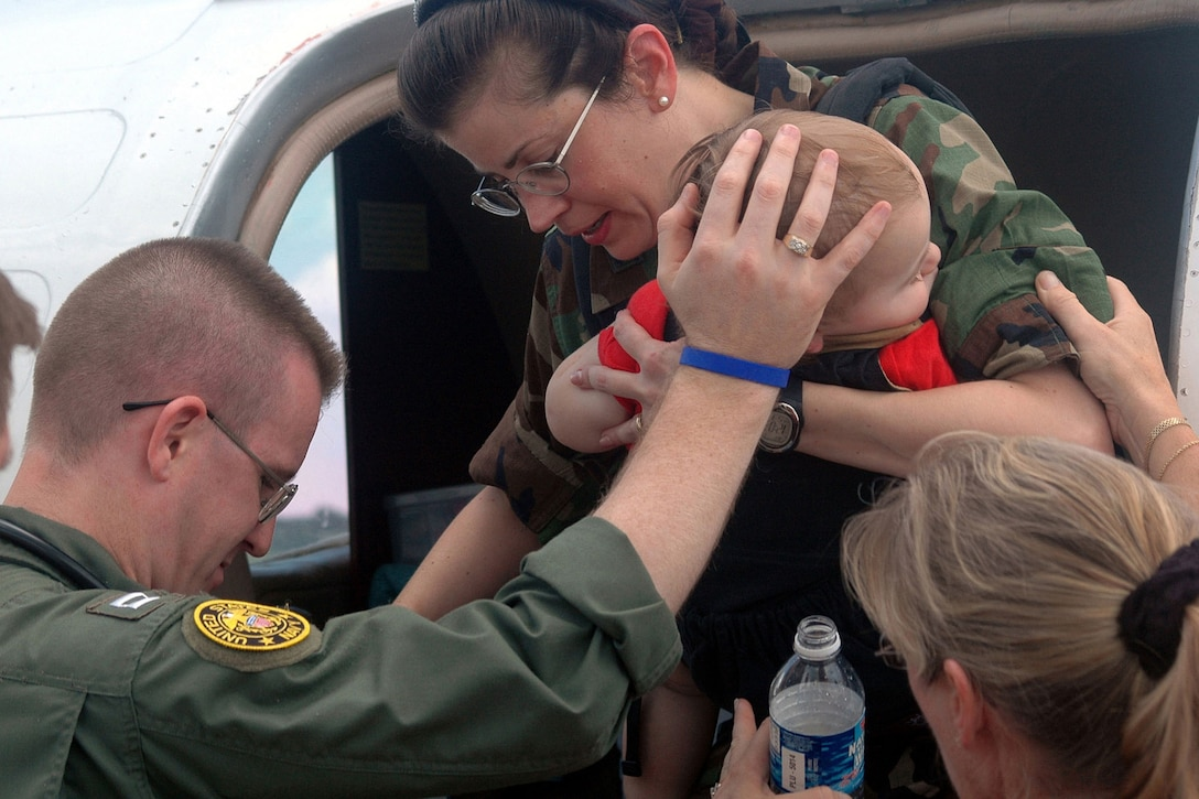 Navy Lt. Larry Anderson helps Air Force Col. Norma Allgood and her 15-month-old son out of an aircraft on Naval Air Station Jacksonville, Fla., Aug. 31, 2005. Allgood and her family, assigned to Keesler Air Force Base in Biloxi, Miss., were medically evacuated from the area after Hurricane Katrina devastated the Gulf Coast. Anderson, a flight paramedic, is assigned to the Naval Air Station Jacksonville Branch Medical Center. U.S. Navy photo by Miriam S. Gallet