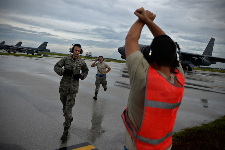 Senior Airman Taylor Giordano, right, signals to the pilot on a U.S. Air Force B-52 Stratofortress, as his wingmen Senior Airman Logan Turner, left, and Staff Sgt. Stephen Cole get into position to launch their aircraft Aug. 22, 2015, at Andersen Air Force Base, Guam. The Airmen are B-52 crew chiefs assigned to the 20th Expeditionary Aircraft Maintenance Squadron from Barksdale Air Force Base, Louisiana. Bomber crews with the 20th Expeditionary Bomb Squadron are part of U.S. Pacific Command's continuous bomber presence and support ongoing  operations in the Indo-Asia-Pacific region. (U.S. Air Force photo by Staff Sgt. Alexander W. Riedel/Released)