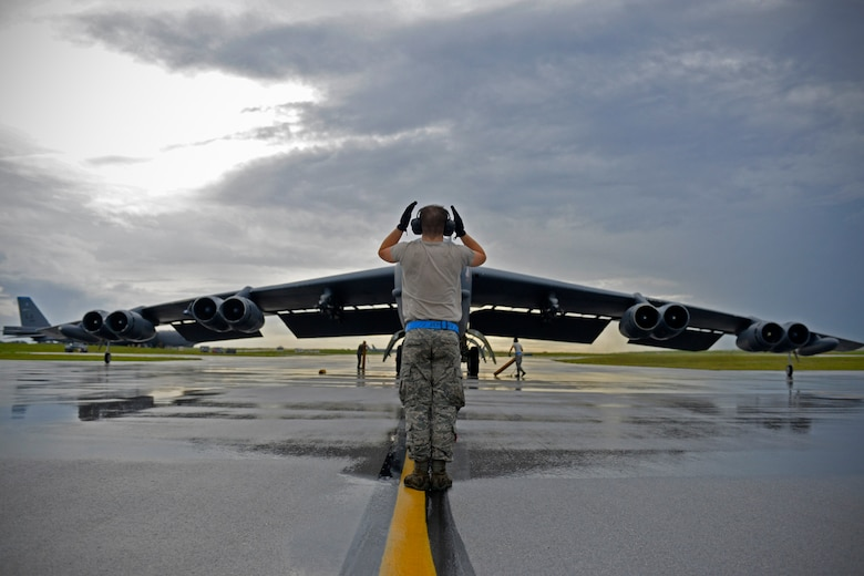 A U.S. Air Force B-52 Stratofortress crew chief assigned to the 20th Expeditionary Aircraft Maintenance Squadron marshals his aircraft on the flightline Aug. 22, 2015, at Andersen Air Force Base, Guam. Bomber crews with the 20th Expeditionary Bomb Squadron from Barksdale Air Force Base, Louisiana, are part of U.S. Pacific Command's continuous bomber presence and support ongoing operations in the Indo-Asia-Pacific region. (U.S. Air Force photo by Staff Sgt. Alexander W. Riedel/Released)