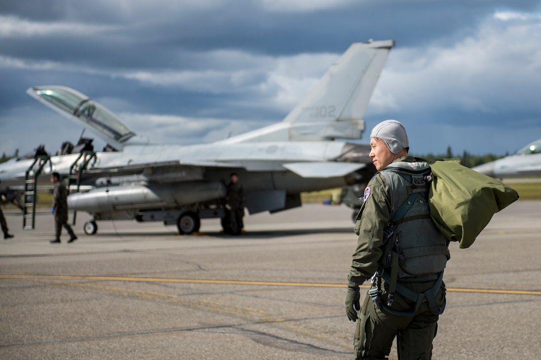 Republic of Korea Air Force (ROKAF) Maj. Lee Dong Seop, a ROKAF F-16D Fighting Falcon pilot, carries equipment to his aircraft, Aug. 11, 2015, prior to the launch of a RED FLAG-Alaska (RF-A) 15-3 sortie from Eielson Air Force Base, Alaska. The ROKAF flew a squadron of F-16Ds across the Pacific Ocean to train in the Joint Pacific Alaska Range Complex's 67,000 square miles of airspace for two weeks of realistic combat flying training throughout RF-A 15-3. (U.S. Air Force photo by 1st Lt. Elias Zani/Released)