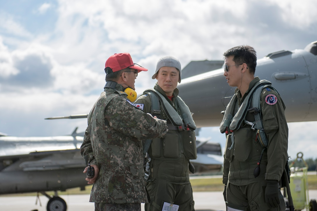 Republic of Korea Air Force (ROKAF) Majs. Lee Dong Seop and Lee Jong Won, both ROKAF F-16D Fighting Falcon pilots, receive preflight instruction from Warrant Officer Dongjun Lee, a ROKAF maintenance officer, Aug. 11, 2015, prior to the launch of a RED FLAG-Alaska (RF-A) 15-3 sortie from Eielson Air Force Base, Alaska. The ROKAF flew a squadron of F-16Ds across the Pacific Ocean to train in the Joint Pacific Alaska Range Complex's 67,000 square miles of airspace for two weeks of realistic combat flying training throughout RF-A 15-3. (U.S. Air Force photo by 1st Lt. Elias Zani/Released)