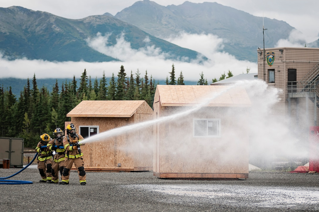 JOINT BASE ELMENDORF-RICHARDSON, Alaska -- Members of the Alaska Air National Guard's 176th Fire Emergency Services practiced fire suppression techniques alongside counterparts from Palmer and Chugiak fire departments here Aug. 16, 2015. Many of the Air Guardsmen work as either fulltime or volunteer employees of fire departments in Alaska, and training with their counterparts in a combined environment helped further develop their knowledge base. (U.S. Air National Guard photo by Staff Sgt. Edward Eagerton/released)