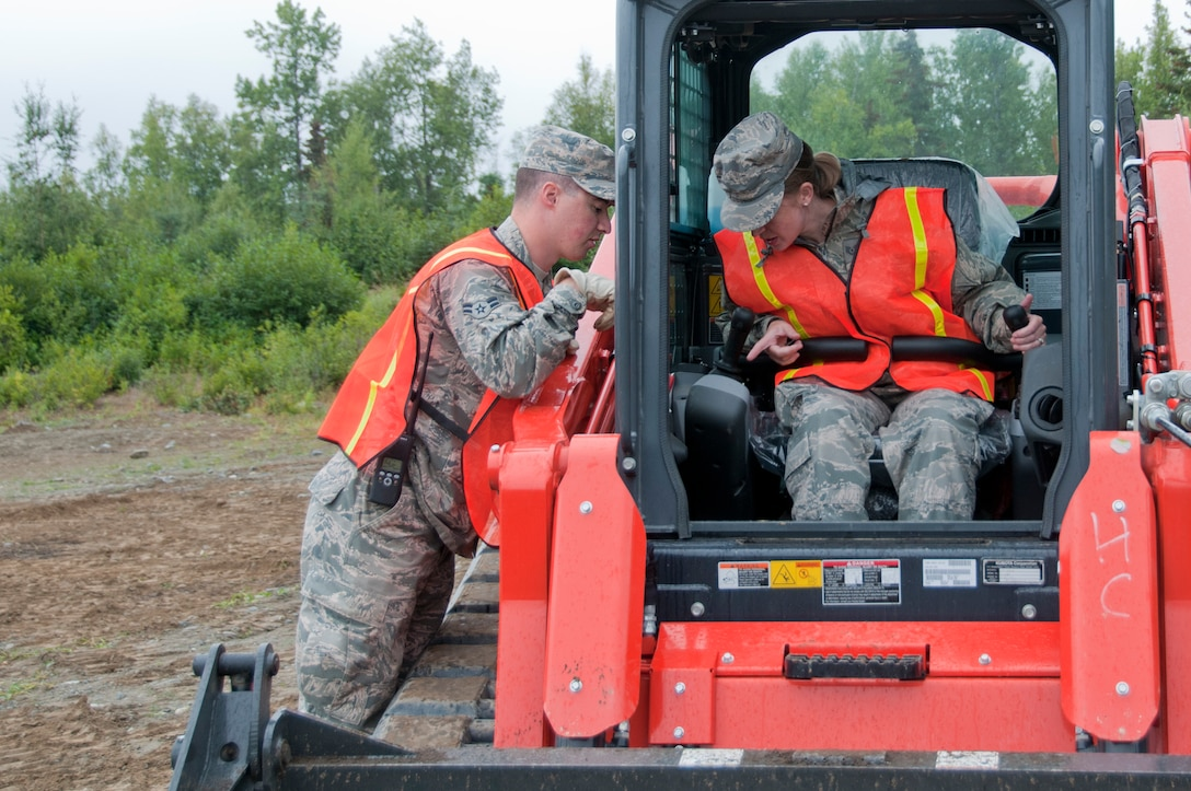 JOINT BASE ELMENDORF-RICHARDSON, Alaska -- Members of the 176th Civil Engineer Squadron practice operating a skid steer here Aug. 16, 2015, during the Polar Guard 15-1 exercise. Skills like this are a part of both their wartime mission and the state mission of urban search and rescue. (U.S. Air National Guard photo by Tech. Sgt N. Alicia Halla/ Released)