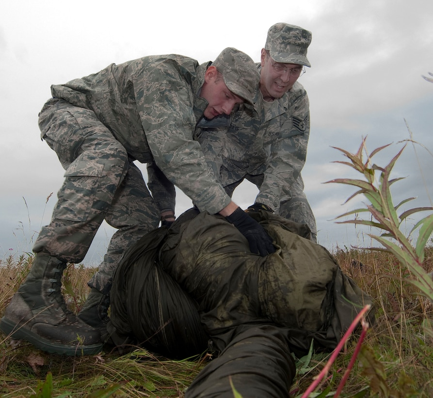 JOINT BASE ELMENDORF-RICHARDSON, Alaska -- Staff Sgt. Josef Lenz (left) and Staff Sgt. Steven Ellis (right), members of the 176th Logistics Readiness Squadron - Air Terminal Operations, recover a deployed cargo parachute after an airdrop at Malamute Drop Zone here, Aug. 16, 2015. Members of the 176th Mission Support Group from approximately 20 different job specialties trained in their wartime mission skills during the four-day Polar Guard 15-1 exercise. (U.S. Air National Guard photo by Capt. John Callahan/ Released.)