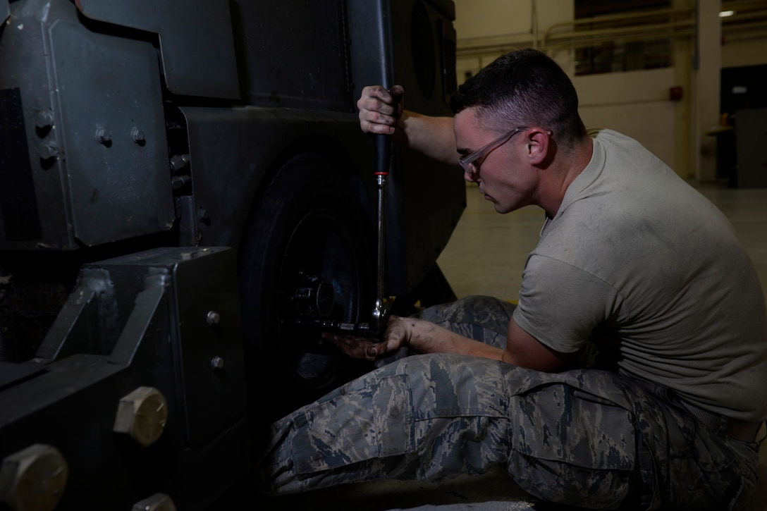 Senior Airman Sean Matkosky, aerospace ground equipment journeyman and deployed member of the 36th Maintenance Squadron, changes a tire on a bomb lift Aug. 12, 2015, at Andersen Air Force Base, Guam. The AGE maintainers care for a variety of essential equipment used during aircraft maintenance and preflight operations. (U.S. Air Force photo by Staff Sgt. Alexander W. Riedel/Released)