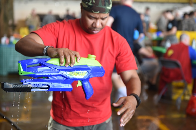 Buckley firefighters spray Combat Dining Out attendees during the event Aug. 21, 2015, at Hangar 909 on Buckley Air Force Base, Colo. Combat Dining Out is an annual event that included water fights, an obstacle course, a grog bowl, food, music, and is a spin on the more formal Combat Dining In, allowing spouses and guests to attend. (U.S. Air Force photo by Airman 1st Class Samantha Meadors/Released)