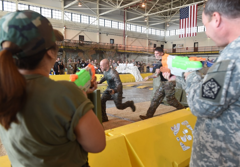 Two Combat Dining Out attendees race in the obstacle course during the event Aug. 21, 2015, at Hangar 909 on Buckley Air Force Base, Colo. Combat Dining Out is an annual event that included water fights, an obstacle course, a grog bowl, food, music, and is a spin on the more formal Combat Dining In, allowing spouses and guests to attend. (U.S. Air Force photo by Airman 1st Class Samantha Meadors/Released)