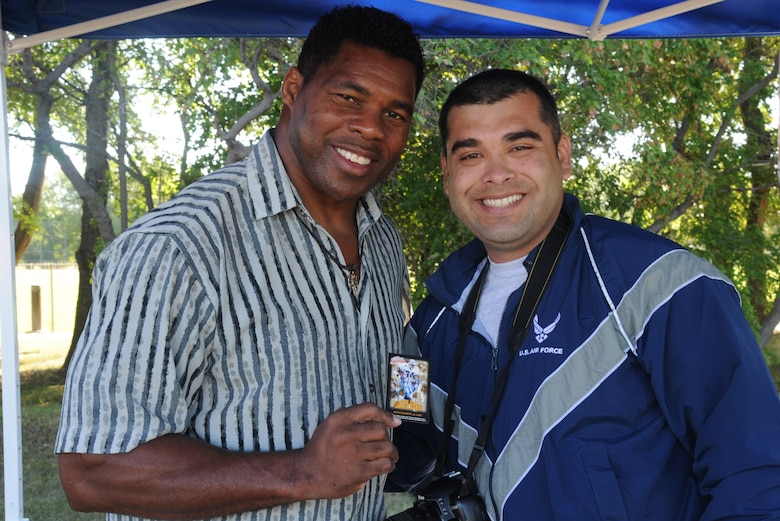 Herschel Walker poses for a photo with Staff Sgt. Luis Loza Gutierrez during a meet and greet session Aug. 20, 2015, at the Summer Bash sports grounds on Grand Forks Air Force Base, N.D. Walker spent the day with Airmen and was the guest speaker at the closing ceremony for the day's events. (U.S. Air Force photo/Senior Airman Desiree Economides)