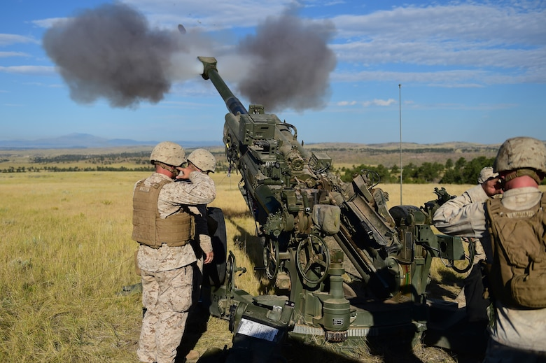 Marines from Quebec Battery, 5th Battalion 14 Marines, fire a round out of a M777 A2 Howitzer during a training exercise Aug. 15, 2015, in Guernsey, Wyoming. Q Battery, a Marine reserve artillery battery, conducted a live-fire exercise for four days to gain proficiency in their craft. (U.S. Air Force photo by Airman 1st Class Luke W. Nowakowski/Released)