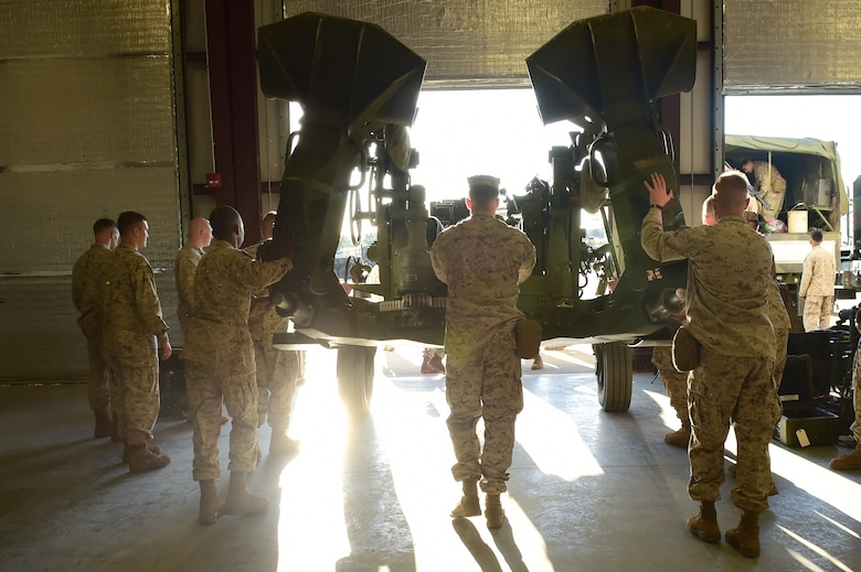Marines from Quebec Battery, 5th Battalion 14 Marines, push a M777 A2 Howitzer toward an awaiting truck to be hauled up to Camp Guernsey, Wyoming, Aug. 13, 2015, on Buckley Air Force Base, Colo. Q Battery is a Marine reserve unit that stages out Buckley AFB and conducted a three-day live fire exercise in Guernsey, Wyoming. (U.S. Air Force photo by Airman 1st Class Luke W. Nowakowski/Released)