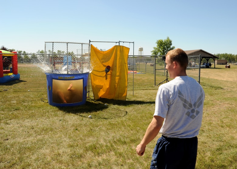 Airman 1st Class Levi Jackson, 319th Comptroller Squadron financial customer service technician, right, celebrates a successful throw at the dunk tank target August 20, 2105, on Grand Forks Air Force Base, North Dakota. The dunk tank at Summer Bash 2015 became the ?Duncan? Tank when Chief Master Sgt. David Duncan, 319th Air Base Wing command chief, volunteered to get dunked. The Airmen?s Activity Council provided the dunk tank for the event. (U.S. Air Force photo by Airman 1st Class Ryan Sparks/Released)