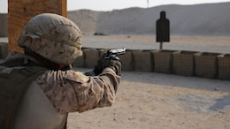 A security forces Marine with Marine Wing Support Squadron-371, Special Purpose Marine Air-Ground Task Force--Crisis Response--Central Command fires after transitioning to his pistol during a live-fire, combat maneuver range in Southwest Asia, August 19, 2015. The live-fire range is designed to emulate realistic combat conditions and force Marines to shoot, move, and communicate to overcome targets at an unknown distance.