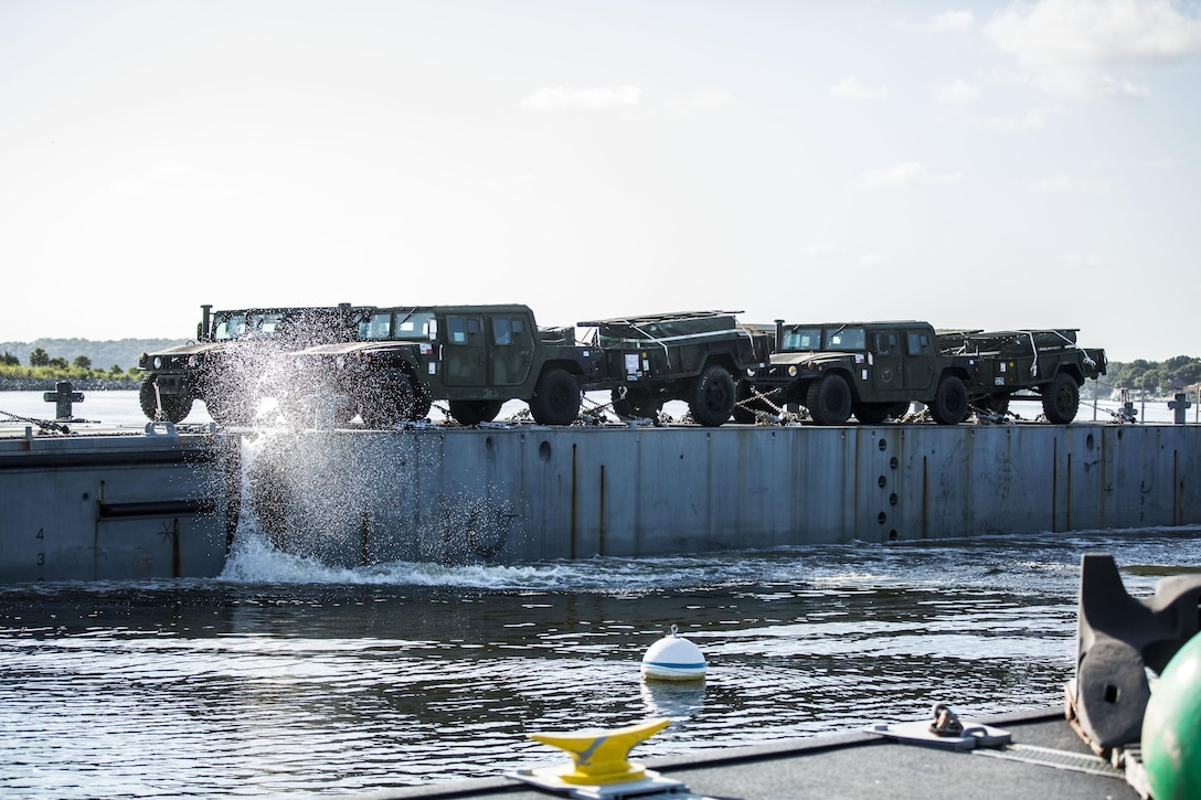 An Improved Navy Lighterage System loaded with vehicles from a recent Marine Expeditionary Unit coasts into the shoreline during a Marine Prepositioning Force Exercise aboard Marine Corps Support Facility Blount Island, Fla., Aug. 10, 2015. Marines with Combat Logistics Regiment 25 teamed up with sailors from Naval Beach Group-2 for the latest iteration of the MPFEX. (U.S. Marine Corps photo by Sgt. Shawn Valosin/Released)