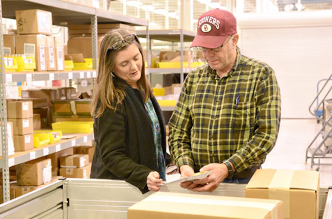 Brenda Price, a Defense Logistics Agency Aviation materials expeditor supervisor, and Kenneth Watkins, another materials expeditor, verify a part before shipping it to a customer Feb. 6.