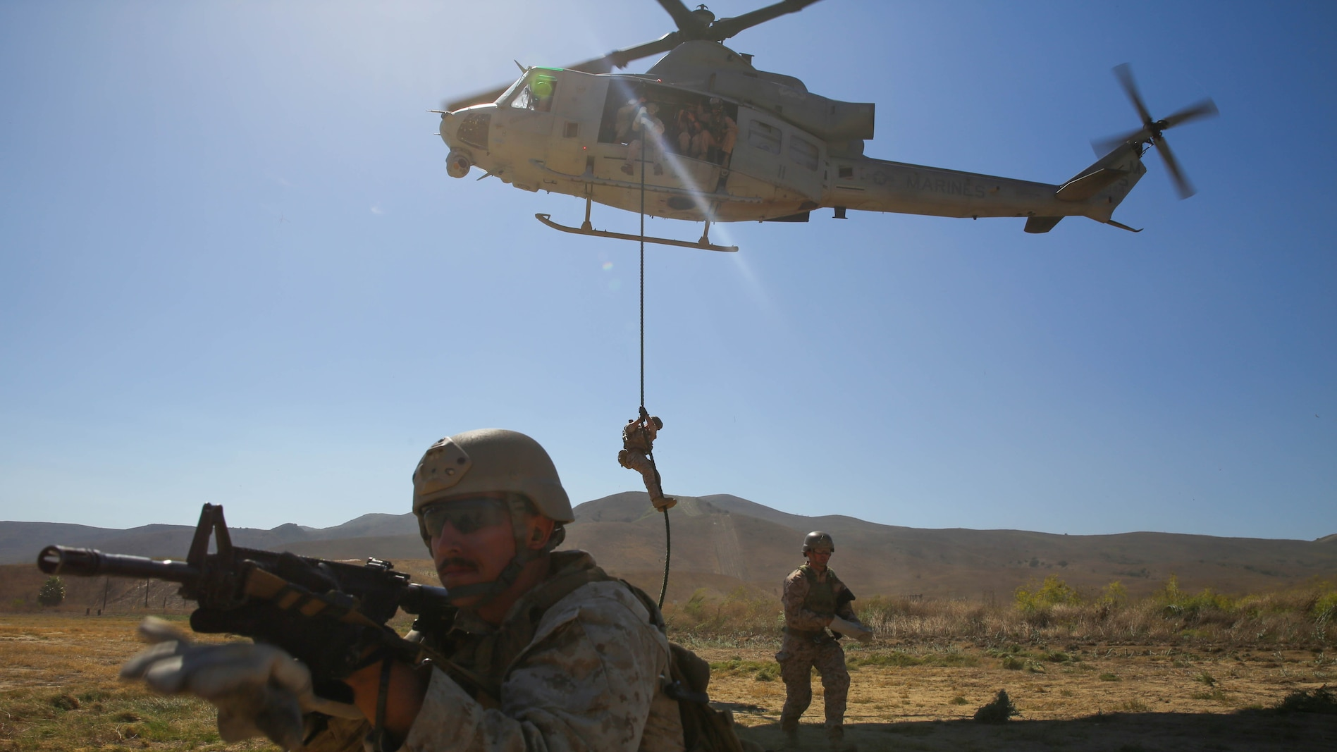 A Marine with Company A, 1st Reconnaissance Battalion, 1st Marine Division, I Marine Expeditionary Force, provides security for his fellow Marines at the drop zone of a fast-roping exercise on Marine Corps Base Camp Pendleton, Calif., Aug 18, 2015. Utilizing both fast-roping and Special Patrol Insertion and Extraction rigging methods, the purpose of the training exercise was to integrate operational coordination between the I MEF Ground Combat Element and Air Combat Element.