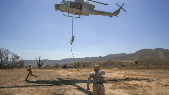 Mechanicsburg, Pa., native Gunnery Sgt. Daniel Young, a platoon sergeant with Company A, 1st Reconnaissance Battalion, 1st Marine Division, I Marine Expeditionary Force, runs to grab the rope underneath a UH-1Y Huey helicopter during a training exercise on Marine Corps Base Camp Pendleton, Calif., Aug. 18, 2015. Utilizing both fast-roping and Special Patrol Insertion and Extraction rigging methods, the purpose of the training exercise was to integrate operational coordination between the I MEF Ground Combat Element and Air Combat Element.