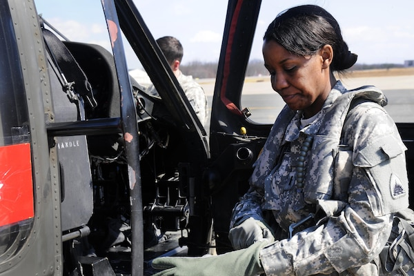 Army 1st Lt. Demetria N. Elosiebo puts on her gear before entering the cockpit of a UH-60 Black Hawk helicopter at Davison Army Airfield, Va., March 15, 2014. Elosiebo is a platoon leader assigned to Company D, Air Ambulance, 1st Battalion, 224th Aviation Regiment. 